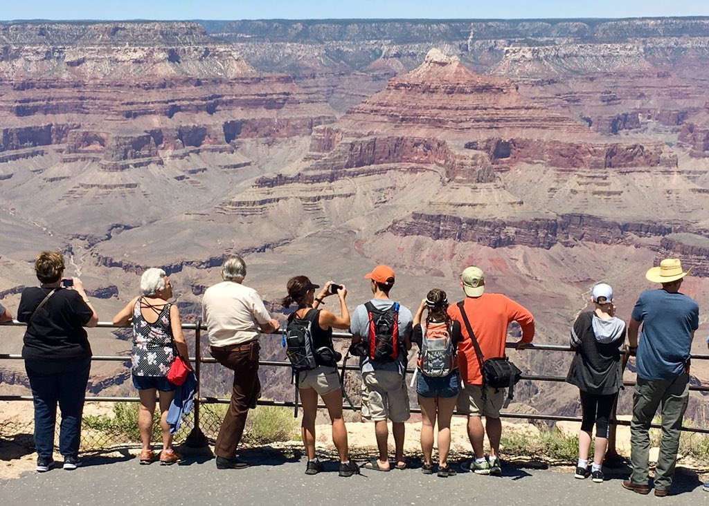 f34997b268 Eight Grand Canyon visitors wearing summer clothing are standing at scenic  overlook behind a railing.